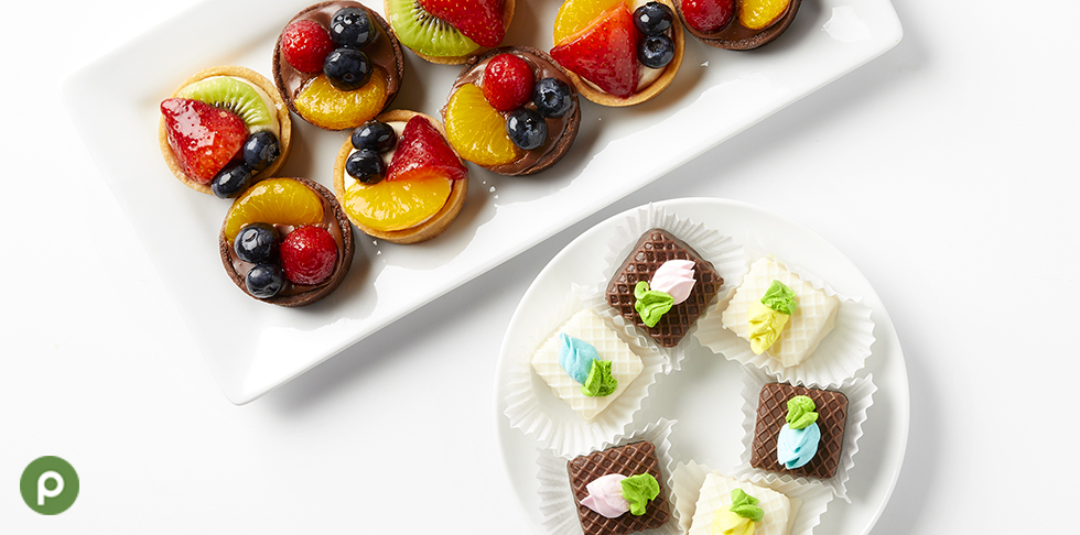 Publix fruit tart and petit fours plated on white surface.