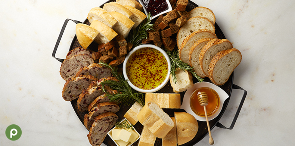 Bread board with variety of Publix Bakery breads, honey and oil with herbs