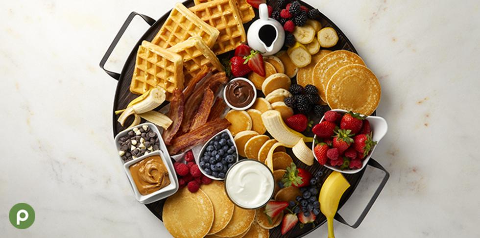 Unique breakfast board with waffles, pancakes, bananas, strawberries, blueberries and yogurt