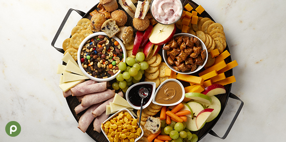 Kid-friendly charcuterie board with sliced meat, cheeses, apple slices, grapes, peanut butter and trail mix.