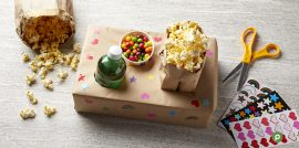 A homemade movie snack tray with a soda bottle, a cup filled with candy and a paper bag filled with popcorn.