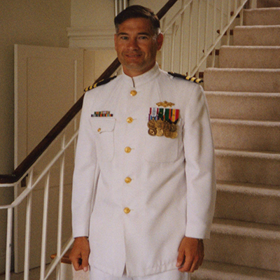 A photo of a man on a set of stairs wearing a white U.S. Navy uniform.