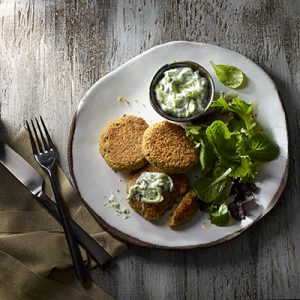 Publix Aprons recipe for Chickpea-Quinoa Patties with Cucumber Sauce plated with leafy on a white plate on top of a wooden table