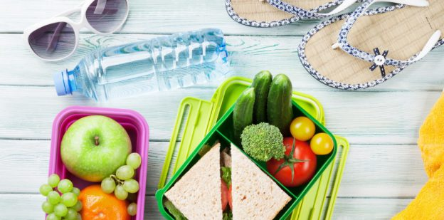 Summer snacks in plastic containers on blue surface.