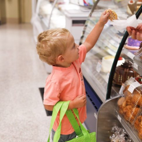Child customer reaching for bakery sprinkle cookie.