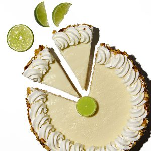 Publix bakery key lime pie with two slices separated and sliced lime wedges on top of a white background