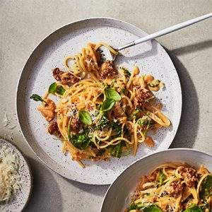 Linguini noodles covered in sauce with greens, sausage and cheese