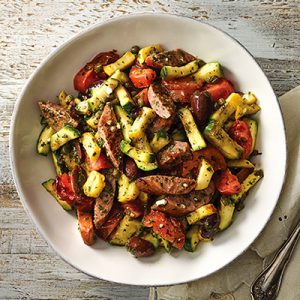 Chopped veggies and sausage covered in herbs in a round white bowl