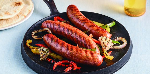Grilled sausages, peppers and onions on a flat skillet pan