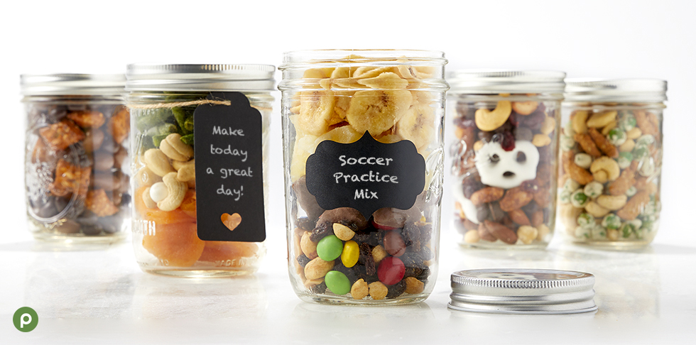 """Mason jars filled custom trail mixed made with various Publix dry produce snacks. Jars labeled with """"make today a great day"""" and """"soccer practice mix."""""""