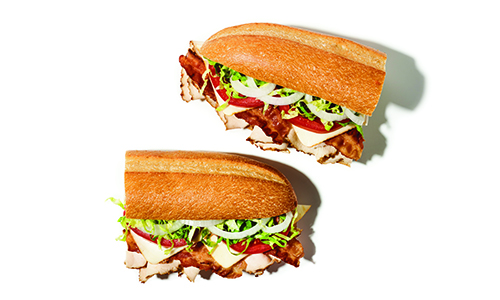 Publix deli smoked rotisserie chicken sub sliced in half on top of a white surface