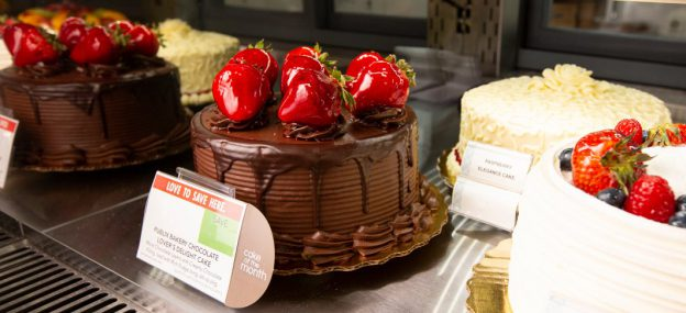 Chocolate supreme cake with strawberries on top in Bakery case at Publix store.