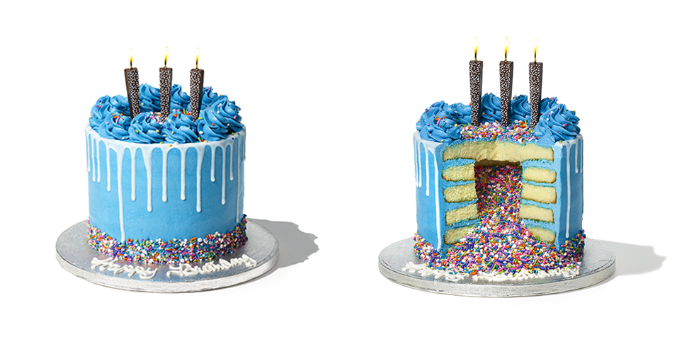 multitiered vanilla cake with blue frosting on top and between layers, filled and topped with rainbow sprinkles and chocolate candles on the top tier