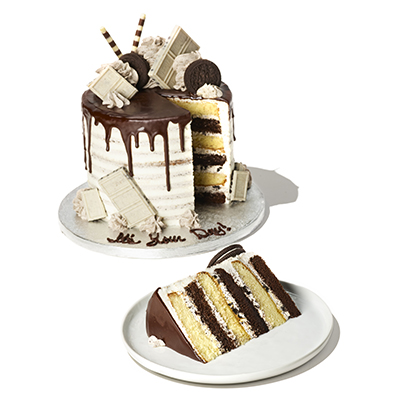 alternating layers of vanilla and chocolate cake with buttercream frosting, a chocolate drizzle, and cookie sandwiches and candies on top