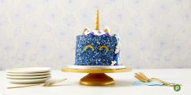 Tall cake covered in multi-shade blue sprinkles with a unicorn horn, ears and eyes on a gold platter, with gold serving utensils and forks.
