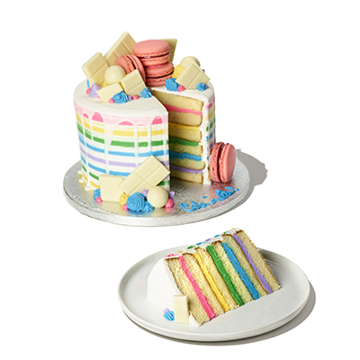 layers of vanilla cake with rainbow frosting in between, topped with pink macarons and white chocolate pieces