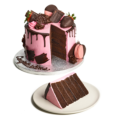 chocolate cake topped with pink icing, a chocolate drizzle, chocolate-covered strawberries and chocolate-dipped macarons