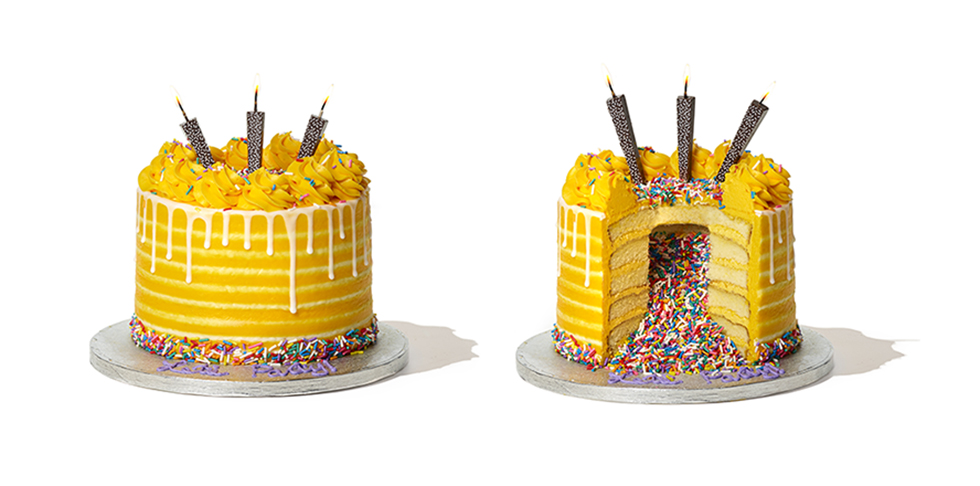 vanilla layer cake covered with yellow frosting, filled and topped with rainbow sprinkles, and topped with three chocolate candles
