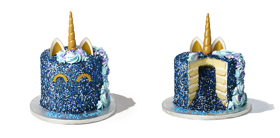 a vanilla tiered cake both filled with and covered by multicolored sprinkles, topped with blue and purple frosting and a golden unicorn horn and ears