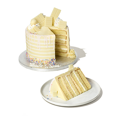 multitiered vanilla cake with buttercream and cream cheese frosting between layers, topped with white chocolate pieces