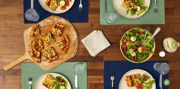 Wooden table with four place settings, a wooden board with a sliced flatbread, a bowl of salad, a stack of napkins and a bottle of ranch