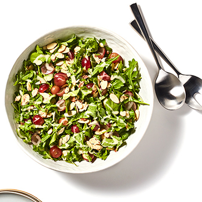 A round white bowl on a white surface with greens, sliced nuts, grapes, and dressing with utensils on the side.