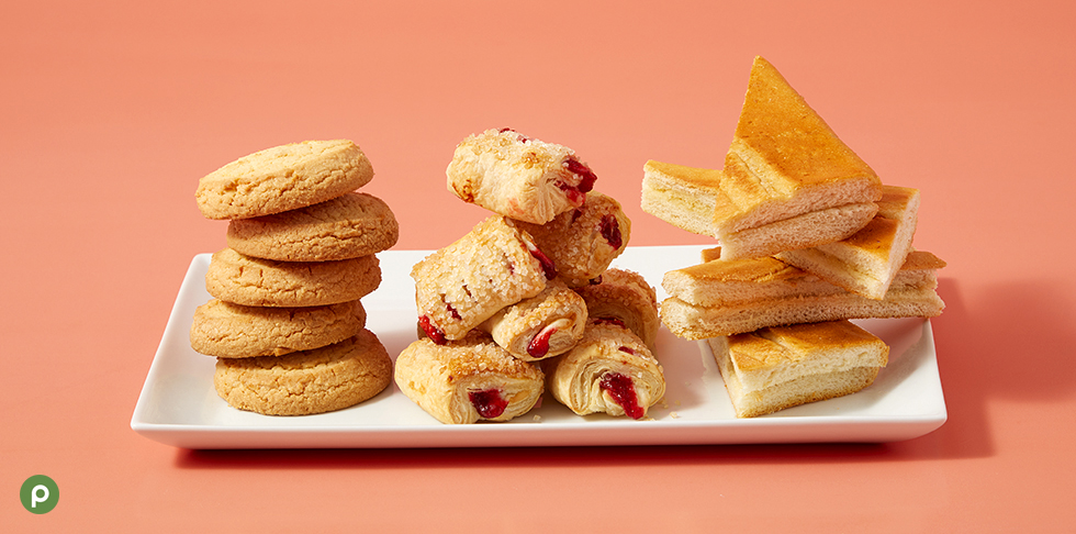 Stacks of Publix Bakery torticas de moron, guava and cheese pastry bites and toasted cuban bread on top of a white plate in front of a bright pink background.