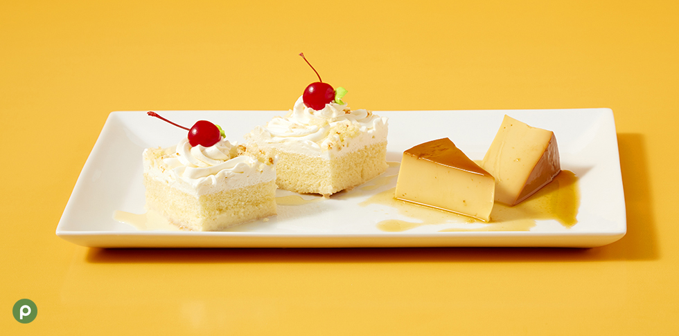 Pieces of Publix Bakery tres leches cake and flan on top of a white plate in front of a bright yellow background