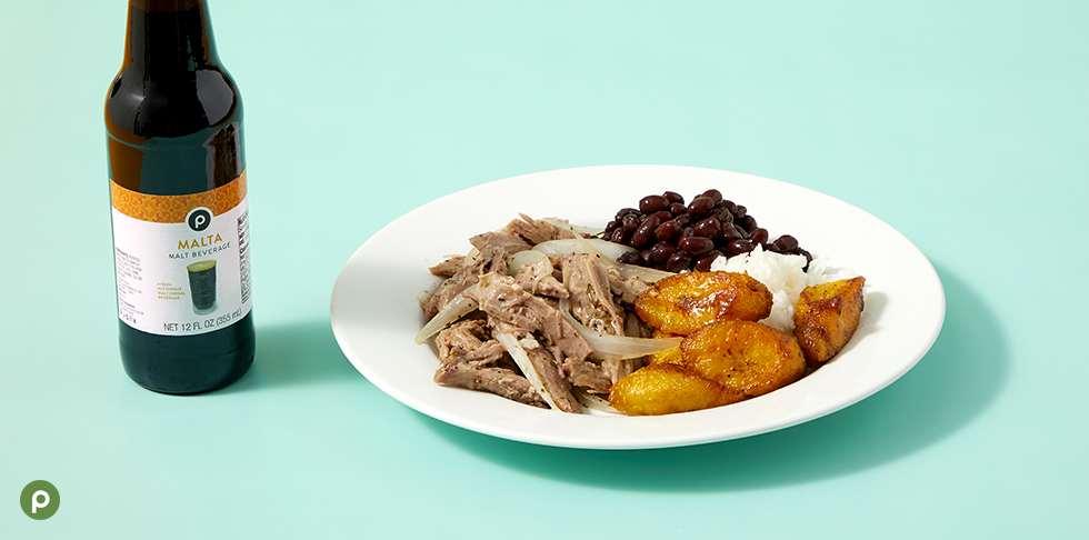 White dinner plate featuring Publix Deli mojo port, Publix platanos maduros, black beans and rice. Accompanied by a bottle of Publix malta in front of a bright teal background