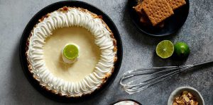 Key Lime Pie on surface with limes, graham crackers