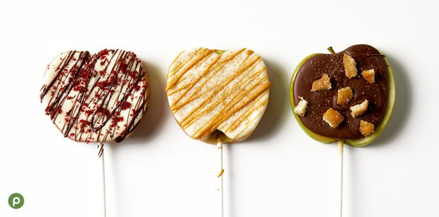 Three sliced apple pieces on sticks covered in white chocolate, red velvet crumbs and dark chocolate; white chocolate and butterscotch; milk chocolate, churro pieces and sugar