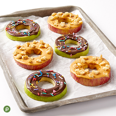 Apple rings on a baking sheet with parchment paper; three covered with milk chocolate and topped with rainbow sprinkles, three covered in butterscotch and topped with pieces of glazed donut.