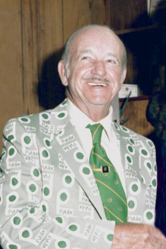 Mr. George wears his logo jacket with a green tie and a smile