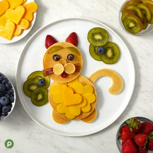 Cat-shaped pancake and fruit creation plated on a white surface