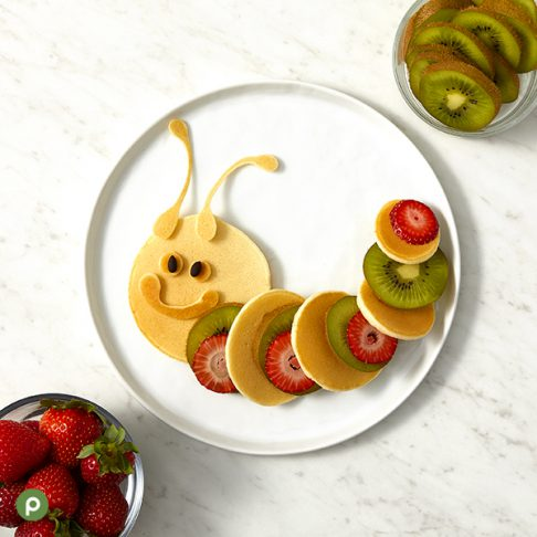Caterpillar-shaped pancake and fruit creation plated on a white surface