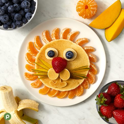 Lion-shaped pancake and fruit creation plated on a white surface
