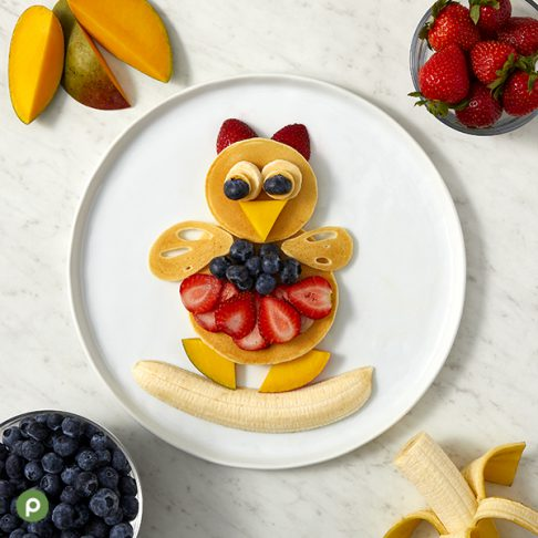 Owl-shaped pancake and fruit creation plated on a white surface