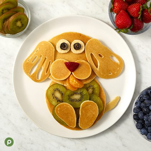 Puppy-shaped pancake and fruit creation plated on a white surface