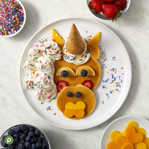 Unicorn-shaped pancake and fruit creation plated on a white surface