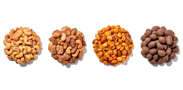 Four piles of flavored nuts and trail mix in a row on a white background