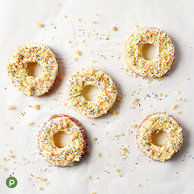 Apple rings on parchment paper covered with white chocolate, sugar cookies crumbs and rainbow sprinkles